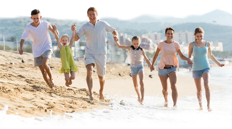 Изображение счастливой семьи бегущей по пляжу